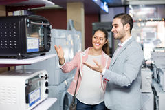 Couple choosing microwave oven Stock Photo