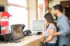 Couple choosing a movie at the theater. Profile view of a young couple buying movie tickets and looking at a screen while deciding what to see Stock Photography