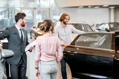 Couple choosing a new car in the showroom. Young couple with salesperson choosing a new car looking on the back seats in the showroom royalty free stock photos
