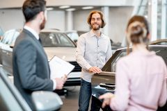 Couple choosing a new car in the showroom. Young couple with salesperson choosing a new car looking on the back seats in the showroom stock images