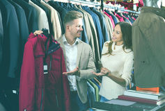 Couple choosing new coat in men's cloths store Stock Images