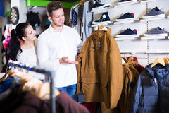 Couple choosing new coat Royalty Free Stock Images