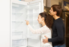 Couple choosing new refrigerator. Two customers looking at large fridges in domestic appliances section royalty free stock image