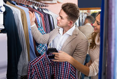 Couple choosing new shirt in men's cloths store Royalty Free Stock Photo