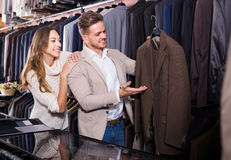Couple choosing new suit in men's cloths store Stock Photography