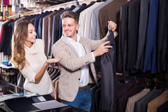 Couple choosing new suit in men's cloths store Royalty Free Stock Images