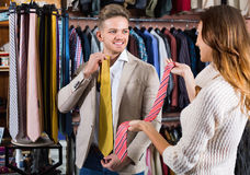 Couple choosing new tie in men's cloths store Royalty Free Stock Photos