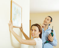 Couple choosing point for picture on wall at home Stock Photos