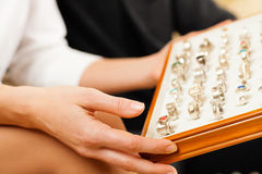 Couple choosing a ring at the jeweller. Couple choosing wedding rings at a jeweller Royalty Free Stock Photo