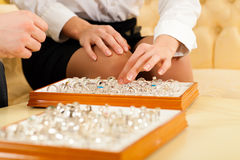 Couple choosing a ring at the jeweller. Couple choosing wedding rings at a jeweller Royalty Free Stock Photos
