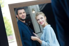 Smiling young couple looking at mirror while choosing suit. In boutique stock image