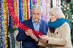 Couple Choosing Tinsels At Store Royalty Free Stock Image