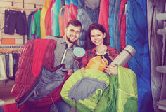 Couple choosing touristic equipment in sports equipment store. Young  positive couple choosing touristic equipment in sports equipment store Stock Image