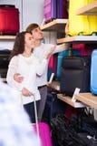 Couple choosing travel suitcase in haberdashery shop Royalty Free Stock Photo