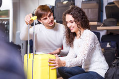 Couple choosing travel suitcase. Man and women choosing travel suitcase in haberdashery store Royalty Free Stock Images