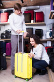 Couple choosing travel suitcase in shop Royalty Free Stock Photography