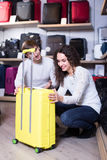 Couple choosing travel suitcase in shop. Smiling young couple choosing travel suitcase in haberdashery shop Royalty Free Stock Photos