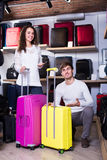 Couple choosing travel suitcase in shop. Young cheerful couple choosing new travel suitcase in haberdashery shop Stock Photo