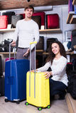 Couple choosing travel suitcase in shop. Young couple choosing new travel suitcase in haberdashery shop Royalty Free Stock Photos