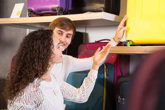 Couple choosing travel suitcase. Two customers choosing travel suitcase in haberdashery shop Stock Photography