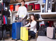 Couple choosing travel suitcase. Young men and women buying travel suitcase in haberdashery shop Stock Photos