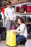 Couple choosing travel suitcase. Young men and women buying new travel suitcase in haberdashery store Royalty Free Stock Photography