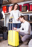 Couple choosing travel suitcase. Young couple choosing new travel suitcase in supermarket Stock Photo