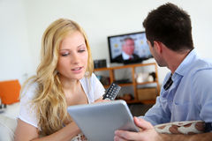 Couple choosing tv program. Young couple choosing tv program on internet Royalty Free Stock Image