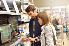 Couple choosing a tv set in supermarket. Couple in department store choosing television set Stock Photo
