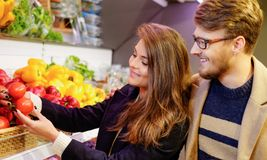 Couple choosing vegetables in grocery store Stock Images