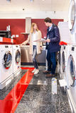 Couple Choosing Washing Machine In Hypermarket Stock Photo