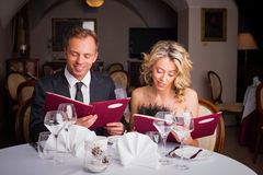 Couple choosing what to eat at restaurant Royalty Free Stock Image