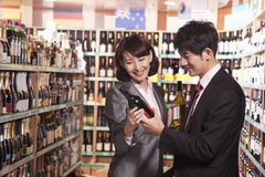 Couple Choosing Wine in a Liquor Store Royalty Free Stock Image