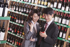 Couple Choosing Wine in a Liquor Store Stock Images