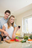 Couple chopping peppers and drinking wine Stock Photo
