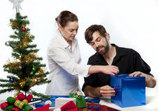 Couple at Christmas. Couple preparing Christmas presents with decorations around them Stock Photos