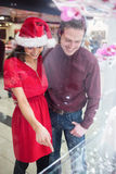 Couple in Christmas attire looking at wrist watch display Stock Photography