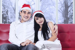 Couple in christmas hat holding hands. Portrait of asian couple wearing santa hat, sitting on sofa while holding hands and smiling on the camera Royalty Free Stock Photography