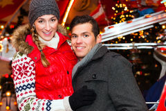 Couple during the Christmas market or advent season. Man and women or a couple or friends during advent season or holiday in front of a carousel or merry-go royalty free stock photo