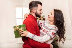 Couple with christmas present. Beautiful smiling women holding christmas present and hugging handsome bearded man Royalty Free Stock Photos
