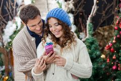 Couple With Christmas Present At Store Royalty Free Stock Photos