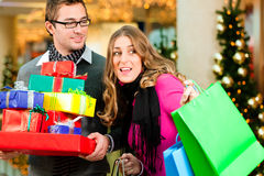 Couple with Christmas presents and bags in mall Stock Photos