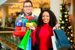 Couple with Christmas presents and bags in mall Royalty Free Stock Images