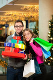 Couple with Christmas presents and bags in shoppin Royalty Free Stock Photos