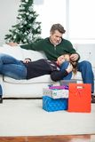 Couple With Christmas Presents Relaxing On Sofa Royalty Free Stock Images