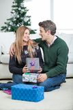 Couple With Christmas Presents Sitting On Floor. Happy mid adult couple with Christmas presents sitting on floor at home Royalty Free Stock Photo