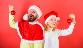 Couple christmas santa costume hold ornament ball. Christmas decoration tradition. Woman and bearded man in santa hat. Couple christmas santa costume hold royalty free stock photo