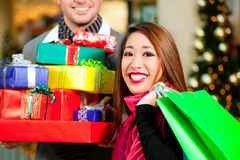 Couple Christmas shopping with presents in mall Stock Photos