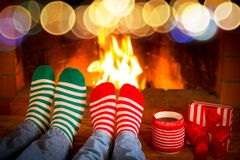 Couple in Christmas socks near fireplace Royalty Free Stock Photography