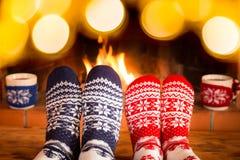 Couple in Christmas socks near fireplace Stock Photos